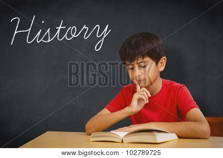 The word history and cute boy reading book in library against blackboard