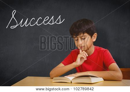 The word success and cute boy reading book in library against blackboard