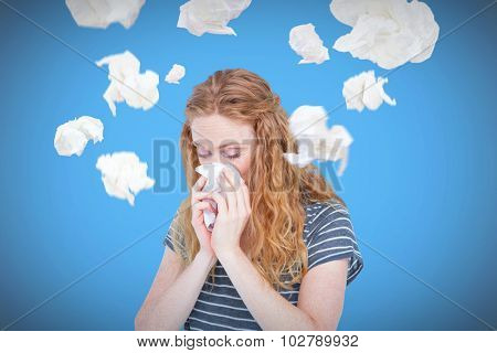 Sick blonde woman blowing her nose against blue background with vignette
