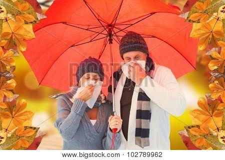 Mature couple blowing their noses under umbrella against autumn scene