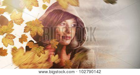 Beautiful woman wearing winter coat looking away against autumn leaves