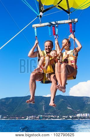 Happy Family Flying On Parachute Over Sea