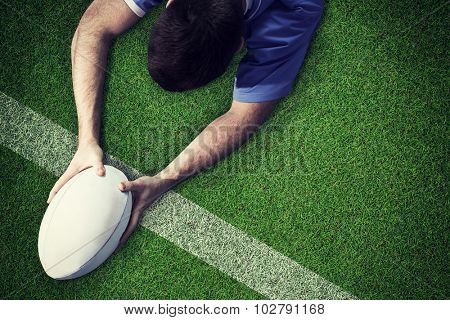A rugby player scoring a try against pitch with line