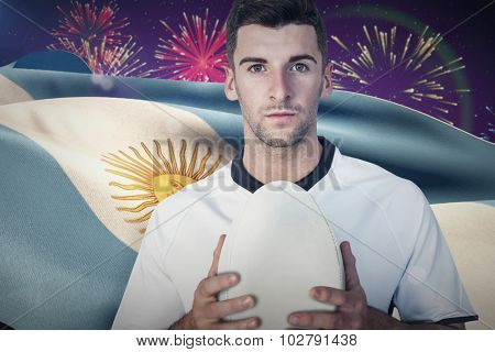 Portrait of a rugby player holding ball against fireworks exploding over football stadium