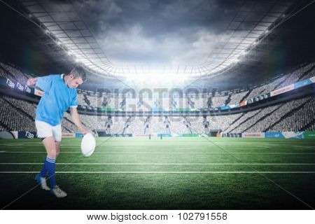 Rugby player kicking a rugby ball against rugby stadium