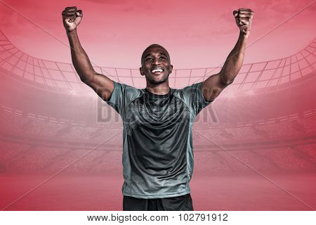 Happy sportsman with clenched fist after victory against red vignette