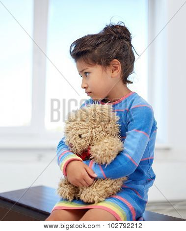 childhood, sadness, loneliness and people concept - sad little girl with teddy bear toy at home