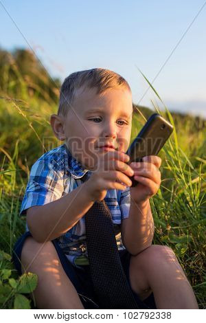 A Child Playing With The Phone