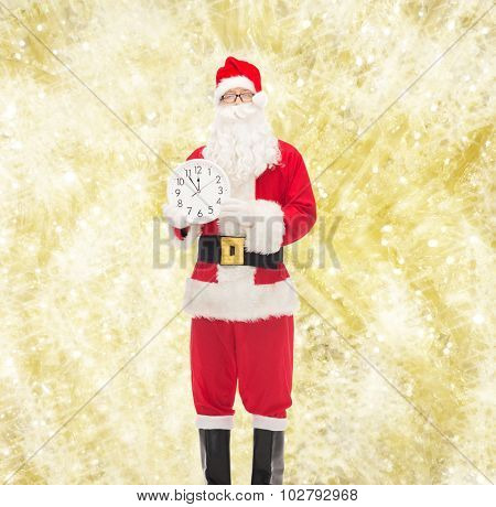 christmas, holidays and people concept - man in costume of santa claus with clock showing twelve over yellow lights background