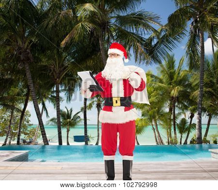 christmas, holidays, travel and people concept - man in costume of santa claus with notepad and bag over swimming pool on tropical beach background