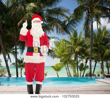 christmas, holidays, gesture, travel and people concept - man in costume of santa claus pointing finger up over tropical beach and swimming pool background
