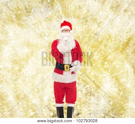christmas, holidays and people concept - man in costume of santa claus making hush gesture over yellow lights background
