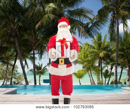 christmas, holidays, travel and people concept - man in costume of santa claus with gift box over swimming pool on tropical beach background