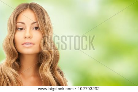 beauty, hair care, people and hairstyle concept - beautiful young woman face with long wavy hair over green natural background