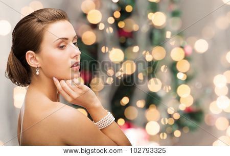beauty, luxury, people, holidays and jewelry concept - beautiful woman with pearl earrings and bracelet over christmas lights background