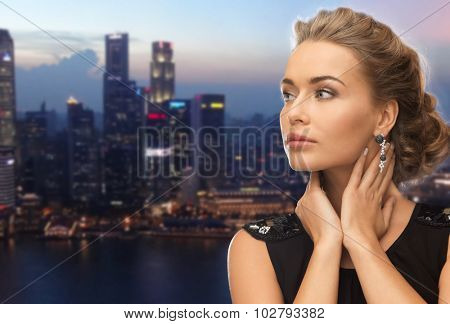 people, holidays, nightlife and glamour concept - beautiful woman wearing earrings over evening singapore city background