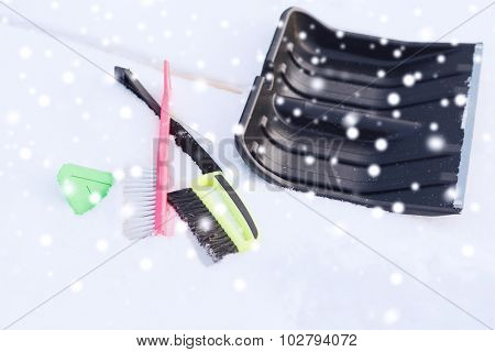 winter and equipment concept - black snowshowel with wooden handle in snow pile