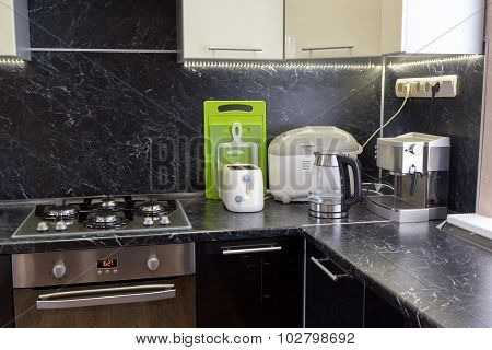 Kitchen Appliances On Black Worktop With Led Backlight