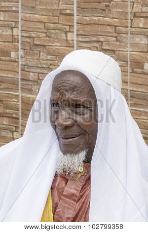 African man smiling in front of his house, eighty years old