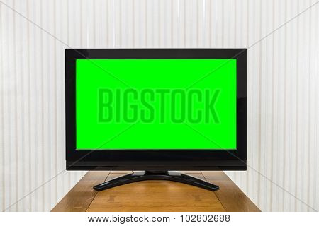 Modern television on wood table with green chroma key screen.