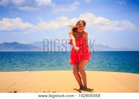 Blond Girl In Red Dances On Sand