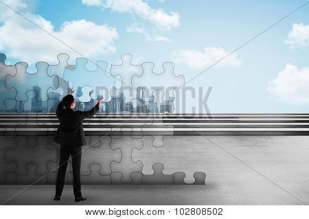 Asian Business Man Holding Piece Of Puzzle Trying To Build A City