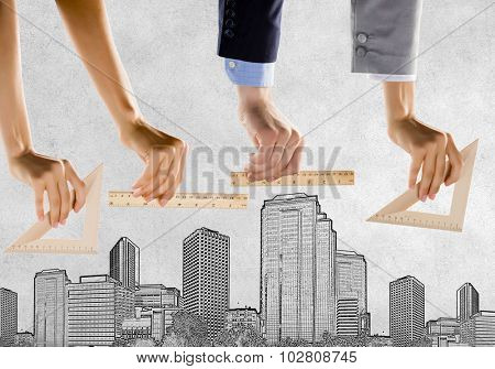 Close up of male hand measuring with ruler model of city