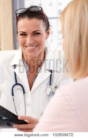 Close up portrait of happy female brunette doctor with patient. Wearing glasses, stethoscope and lab coat. Smiling, looking at camera.