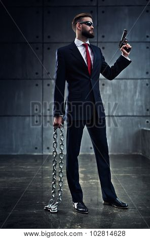 Danger businessman with heavy chain and gun in black suit standing on wall background.