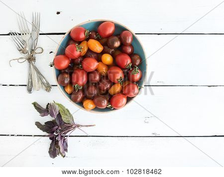 Cherry tomatoes in blue ceramic bowl, vintage silverware and fresh basil leaves on rustic white wood