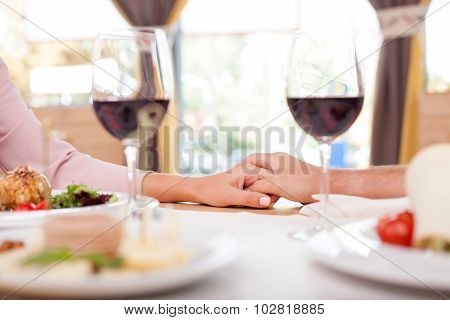 Cute loving couple is dating in restaurant