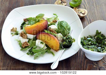 Salad with peaches, arugula, cream cheese, pesto and walnuts