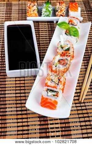 sushi rolls assortment on  plate and chopsticks.
