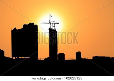Sunset and silhouette construction city with crane on top building.