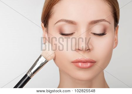 Professional makeup artist is treating attractive girl
