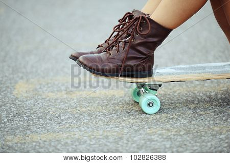 closeup girl with boots sitting on skate board