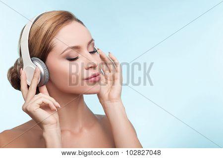 Attractive healthy girl is relaxing with earphones