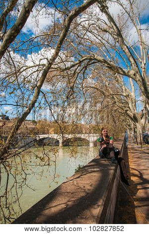 Young Girl Sitting On The Railing Of The Tiber River, Rome, Italy