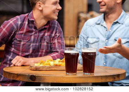 Attractive two male friends are communicating in pub