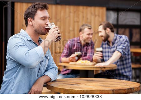 Cheerful young guy is swigging lager in bar