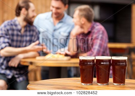 Cheerful young guys are communicating in pub