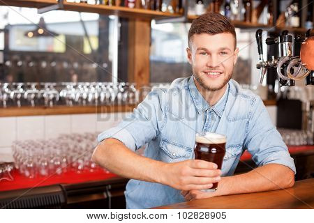 Attractive male barman is working in bar