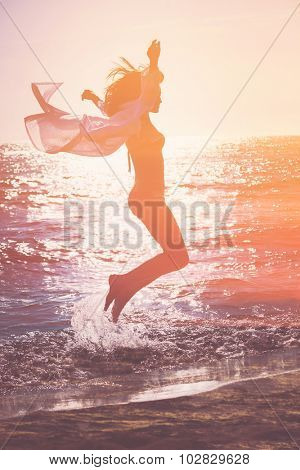 double exposure of a woman jumping against sea at sunset