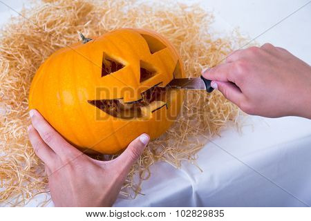 Close Up Of Male Hands Carving Pumpkin Jack-o-lantern For Halloween