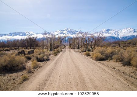 Dirt Road Leads To Snow Covered Sierra Nevada Mountains In Spring