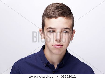 Teen boy looking sad on grey background