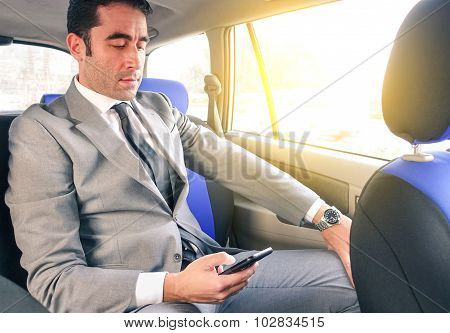 Young Handsome Businessman Sitting In Taxi Cab While Texting Sms With Smartphone - Business Concept