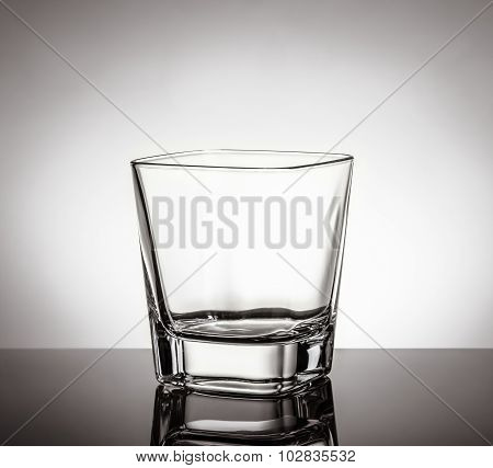 Empty Glass Of Whiskey On Black Table With Reflection On White Background