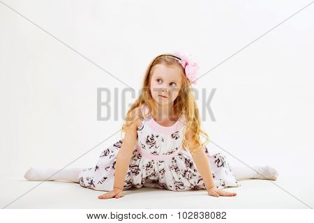 Little Blond Girl Sitting On The Twine In Front Of White Background