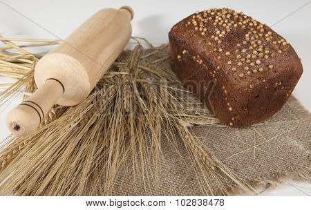 Loaf of homemade bread with black mustard seeds on a table with spikelets of rye and a wooden rolling pin on a background.